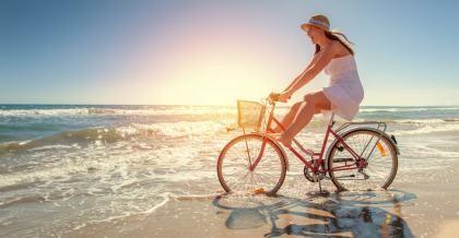 Frau auf einem Fahrrad auf Reisen am Strand