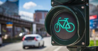 Eine Ampel für Fahrradfahrer an einer befahrenen Straße zeigt grünes Licht.