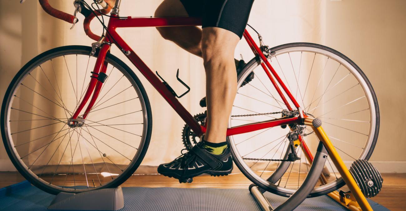 Mann auf einem Fahrrad sitzend, welches in einem Rollentrainer eingesetzt ist.