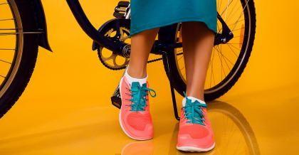 Die Füße einer jungen Frau sind vor einem Fahrrad zu sehen.