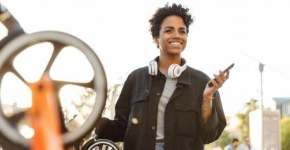 Eine Radfahrerin leiht sich ein Fahrrad über die Bike Sharing App.