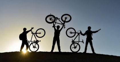 Drei Fahrradfahrer präsentieren ihr Fahrrad als Zeichen für den Klimaschutz.