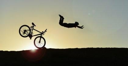 Eine Silhouette im Gegenlicht fliegt wegen zu starker Bremsen über ihr Fahrrad.