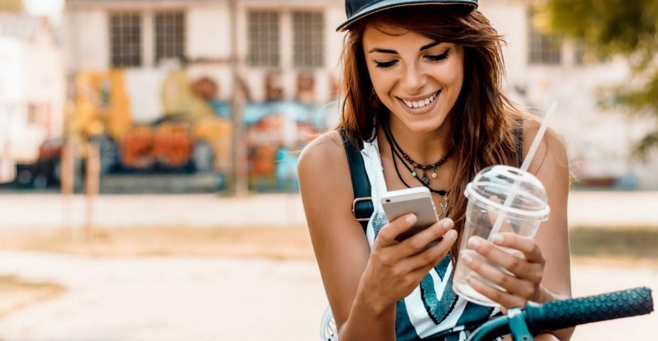 Eine junge Frau benutzt ihr Handy am Fahrrad als Navi und Fitness-Tracker.