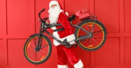 Ein Weihnachtsmann trägt ein Fahrrad als Geschenk.