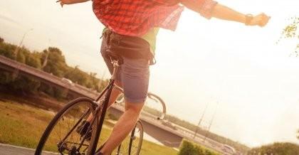 Ein Mann fährt gut gelaunt freihändig in Richtung Sonne und freut sich über seinen Riemenantrieb.