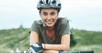 Eine junge Frau mit Fahrradhelm lehnt sich locker auf ihren Lenker und schaut lächelnd in die Kamera.