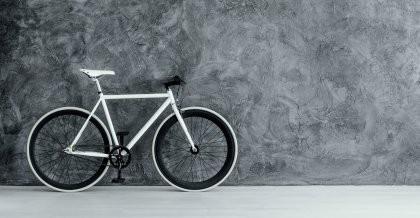 Ein futuristisches Fahrrad mit weißem Rahmen vor einer grauen Wand.