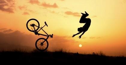 Ein Fahrradfahler hat einen Fahrradunfall und fliegt im hohen Bogen vom Rad. Vor einem Sonnenuntergang ist nur seine Silhouette zu sehen.