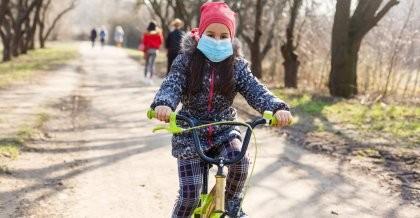 Ein Kind mit Mundschutz fährt auf dem Fahrrad durch den Park