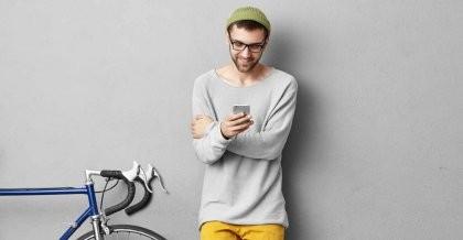 Ein junger Mann steht an die Wand gelehnt mit seinem Handy neben seinem Fahrrad.