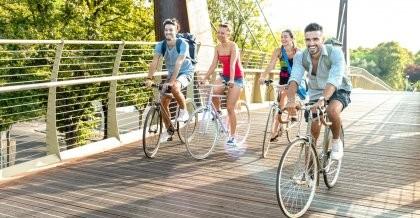 Vier Freunde sind auf dem Rad über eine Brücke unterwegs.