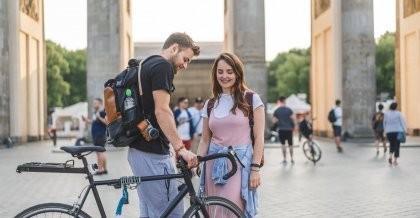 Zwei Freund*innen stehen mit dem Rad am Brandenburger Tor in Berlin.