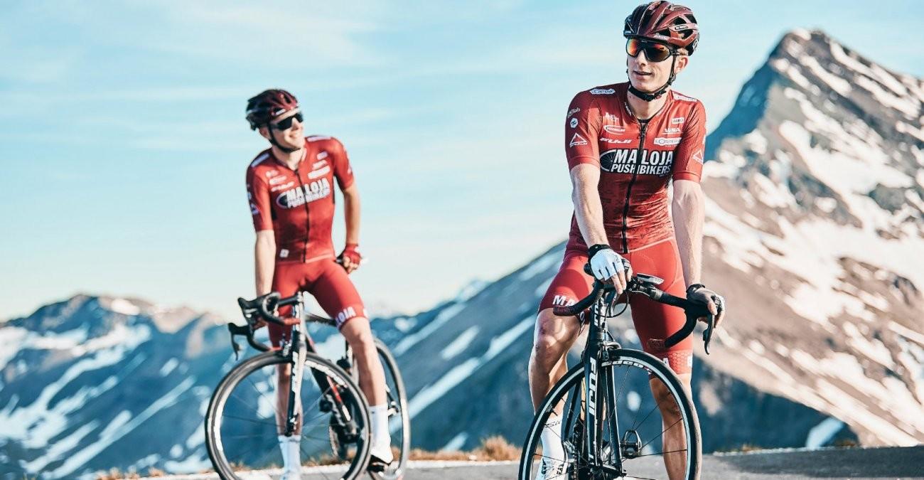 Zwei Radfahrer der Tour de France stehen vor den Alpen.