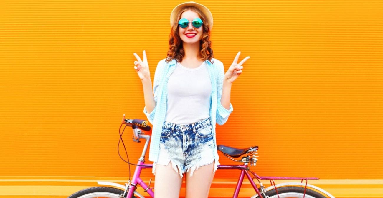Eine junge Frau mit Sonnenbrille und Sonnenhut steht vor ihrem Fahrrad und zeigt das Peace-Zeichen.