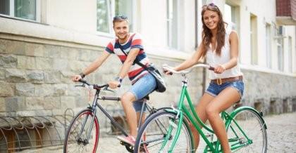 Zwei junge Menschen fahren auf dem Fahrrad durch die Stadt