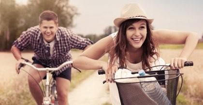 Zwei junge Menschen fahren auf dem Fahrrad mit ihrem Fahrradzubehör durch die Natur.