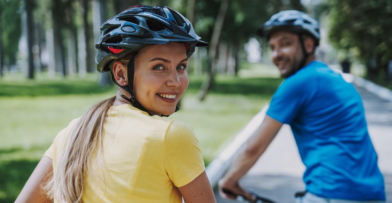 Zwei Fahrradfahrer*innen mit Helm