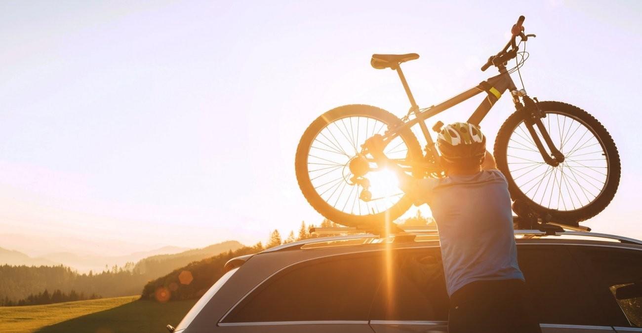 Ein Mann hebt ein Fahrrad im Sonnenuntergang auf ein Autodach.