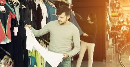 Ein Fahrradfahrer sieht sich ein nachhaltiges T-Shirt in einem Shop an.
