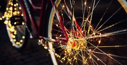 Fahrrad mit Lichterkette behangen auf dunkler Straße