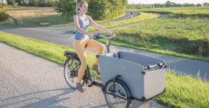 Eine Frau fährt auf einem Radweg mit einem Lastenrad und lächelt dabei zufrieden