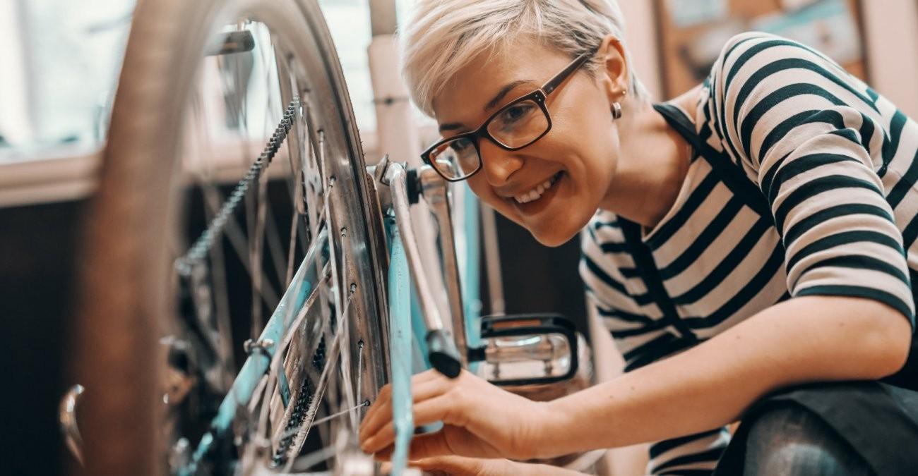 Frau mit Brille bastelt an einem türkisen Fahrrad