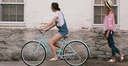 Frau fährt auf einem türkisen Fahrrad im Frühling