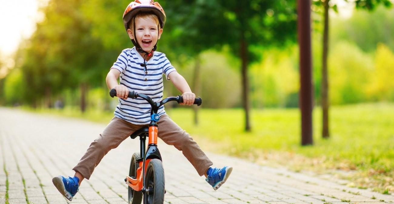Kleiner Junge fährt mit einem Laufrad durch einen Park